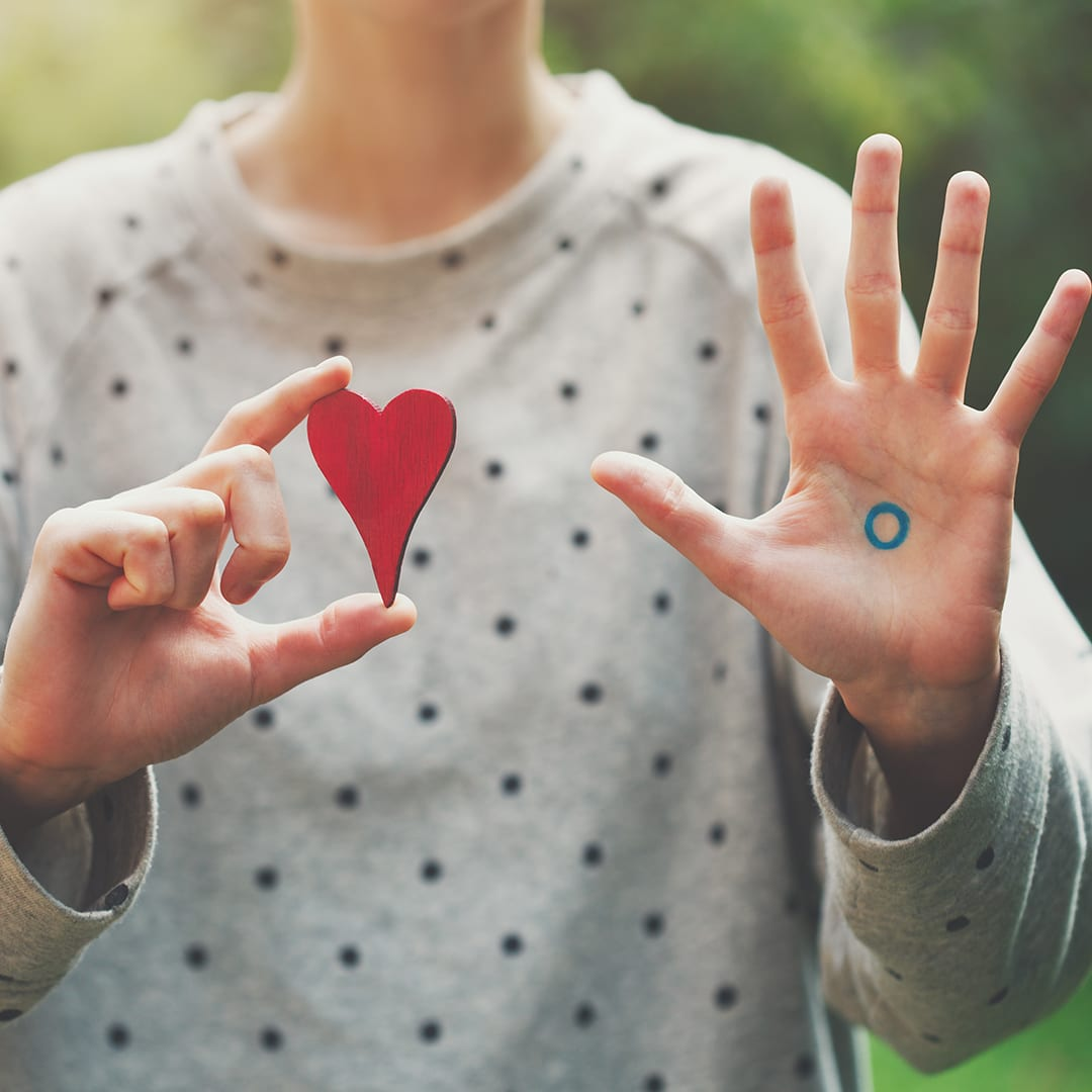 girl holding a heart shape on right hand and showing the blue circle with palm open on the left hand