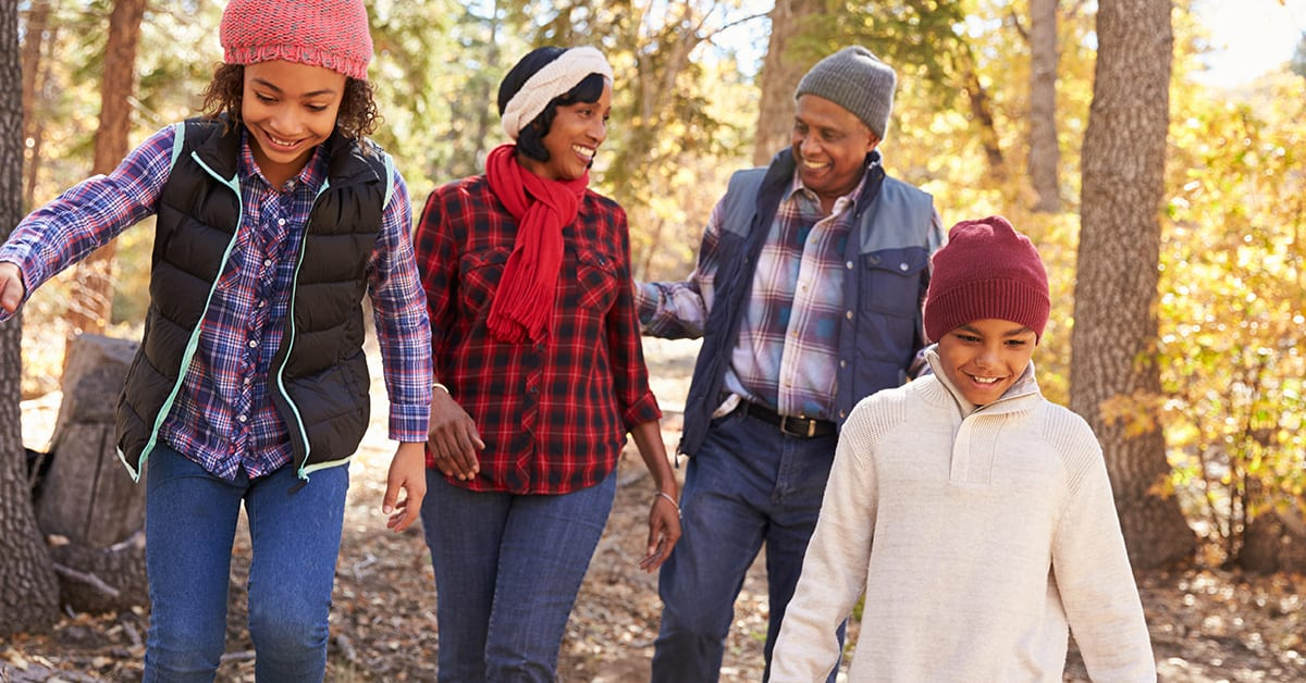 black family of 4 walking in the woods