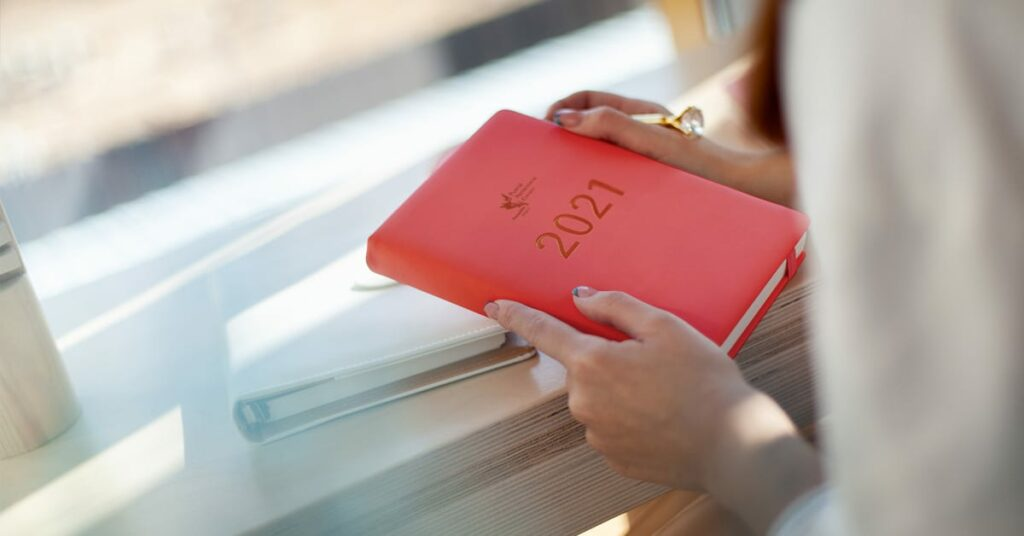 woman holding a red CPP 2021 planner