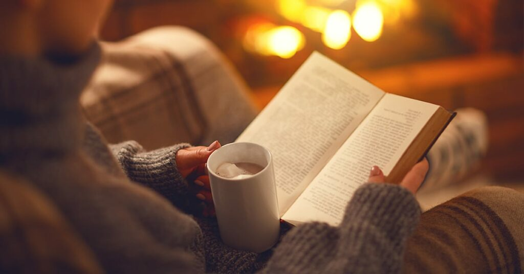woman reading a book with a hot coco on a warm cozy environment