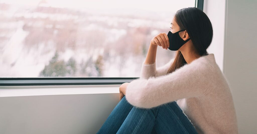 woman with face mask looking outside the window on winter