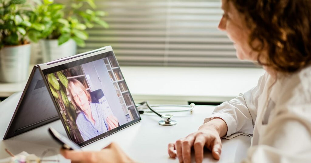telemedicine concept elderly woman using laptop and taking her blood pressure