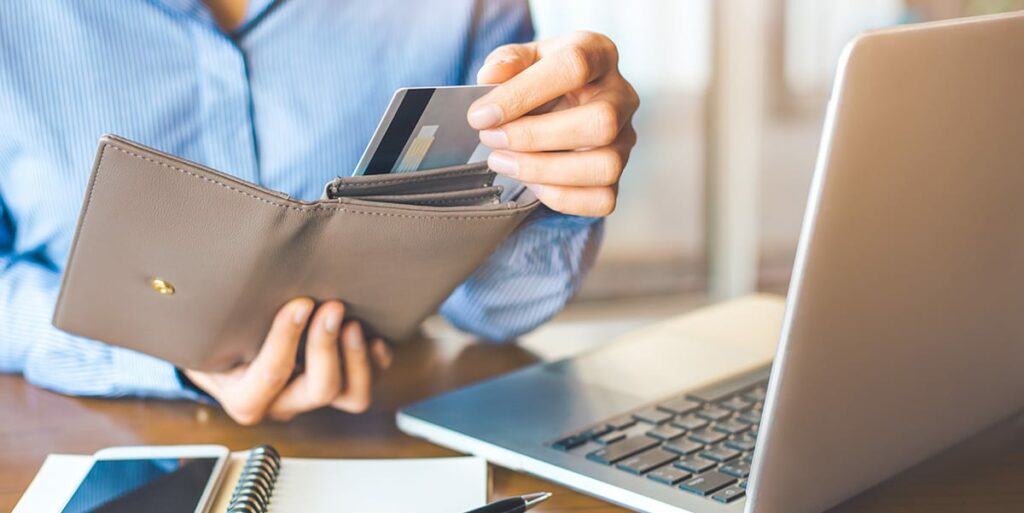 women taking out credit card on wallet to pay off debts