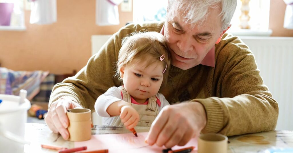 Cute little baby toddler girl and handsome senior grandfather painting with colorful pencils at home. Grandchild and man having fun together