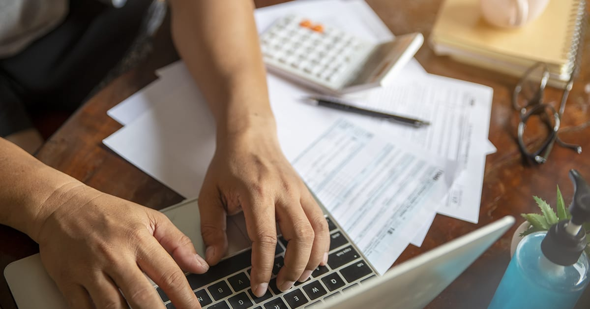 udget and Tax planning concept. Accountant is calculating company's annual tax and typing laptop. Personal income tax form for who have income