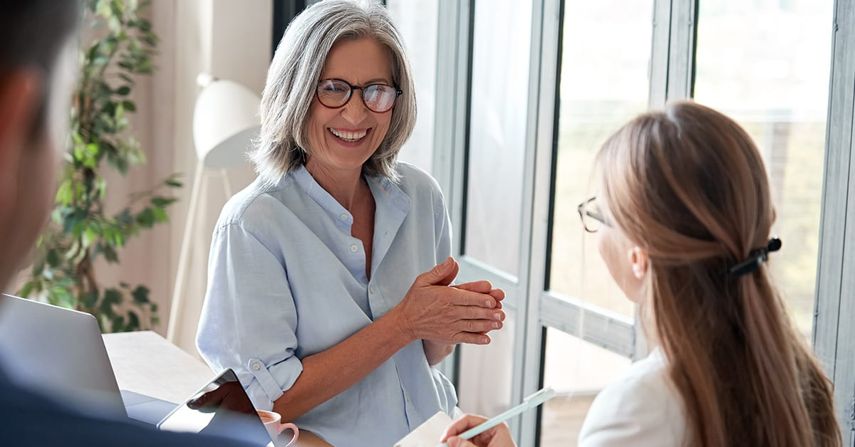 Happy mature old female mentor coach laughing training young interns at group office meeting professional workshop. Cheerful middle aged teacher professor talking to students at university