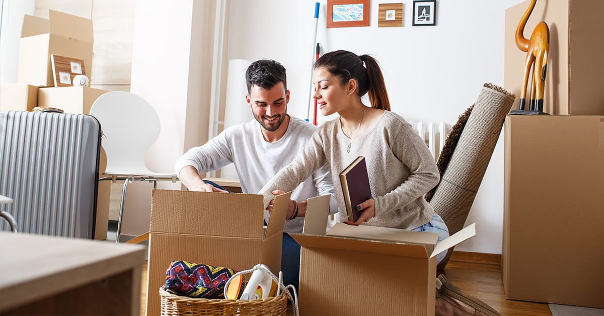 Young couple packing boxing to move new home