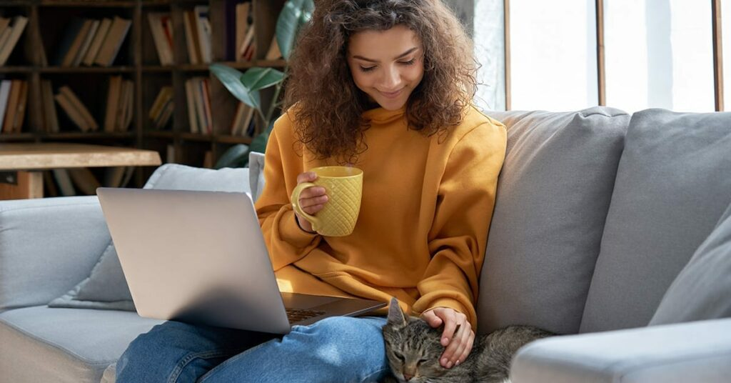 Happy relaxed hispanic teen girl student or freelancer relaxing sitting on couch holding laptop on lap working studying from home drinking tea, playing with cute pet cat in cozy sunny room on sofa.