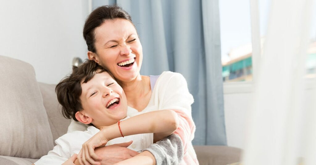 single mother with her son on the sofa laughing