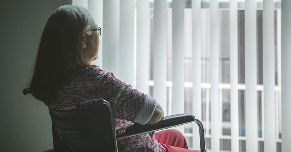 Old woman with stroke on a wheelchair looking out the window