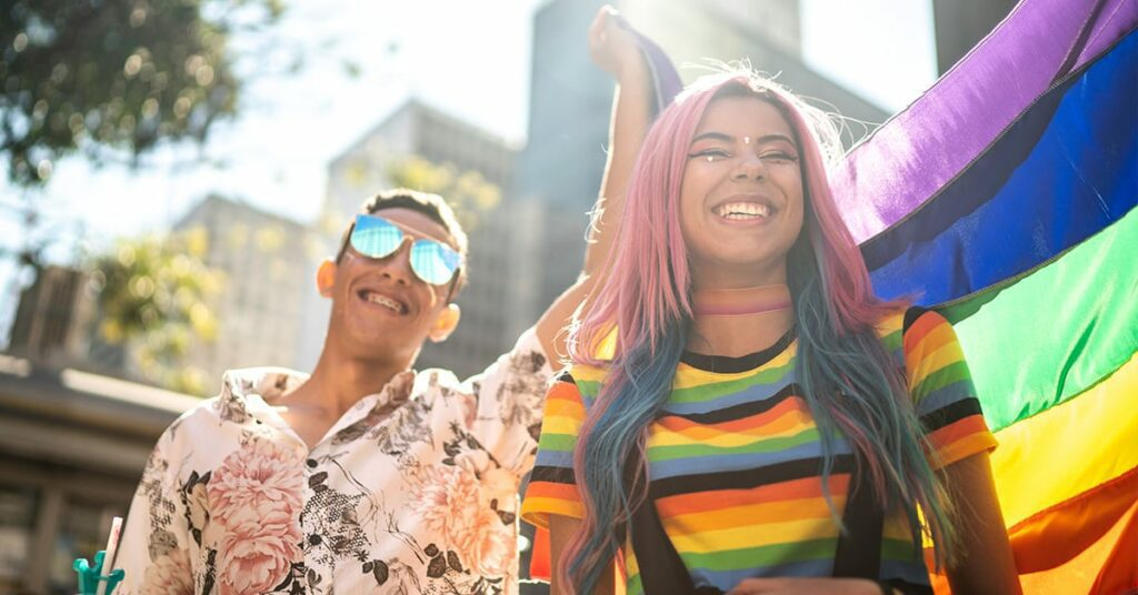 a woman in rainbow shirt and a man holding the pride flag on pride parade