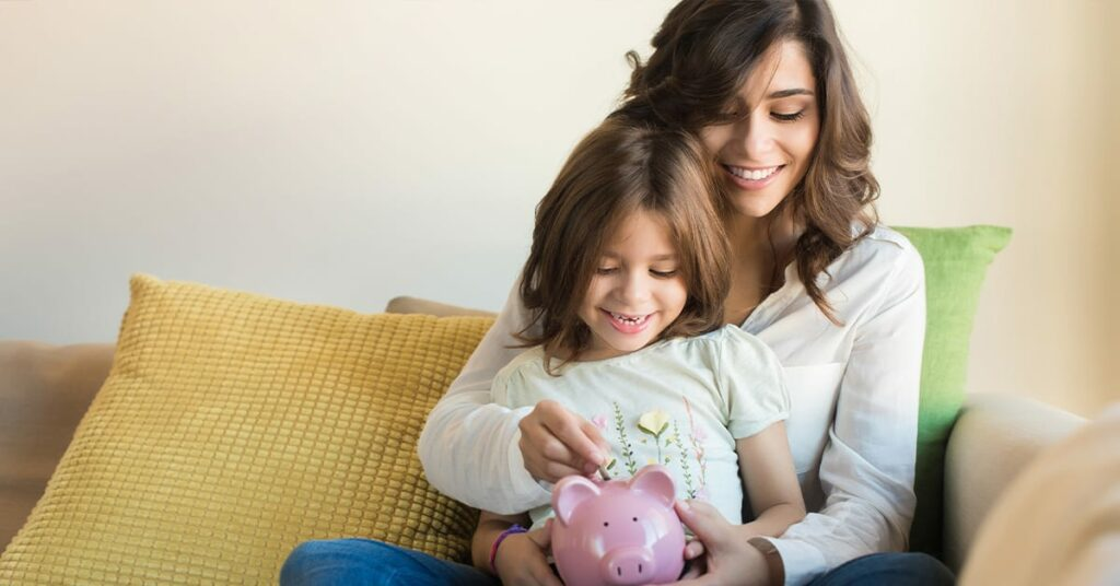 Mother and Daughter on the couch putting coin a pink piggy bank