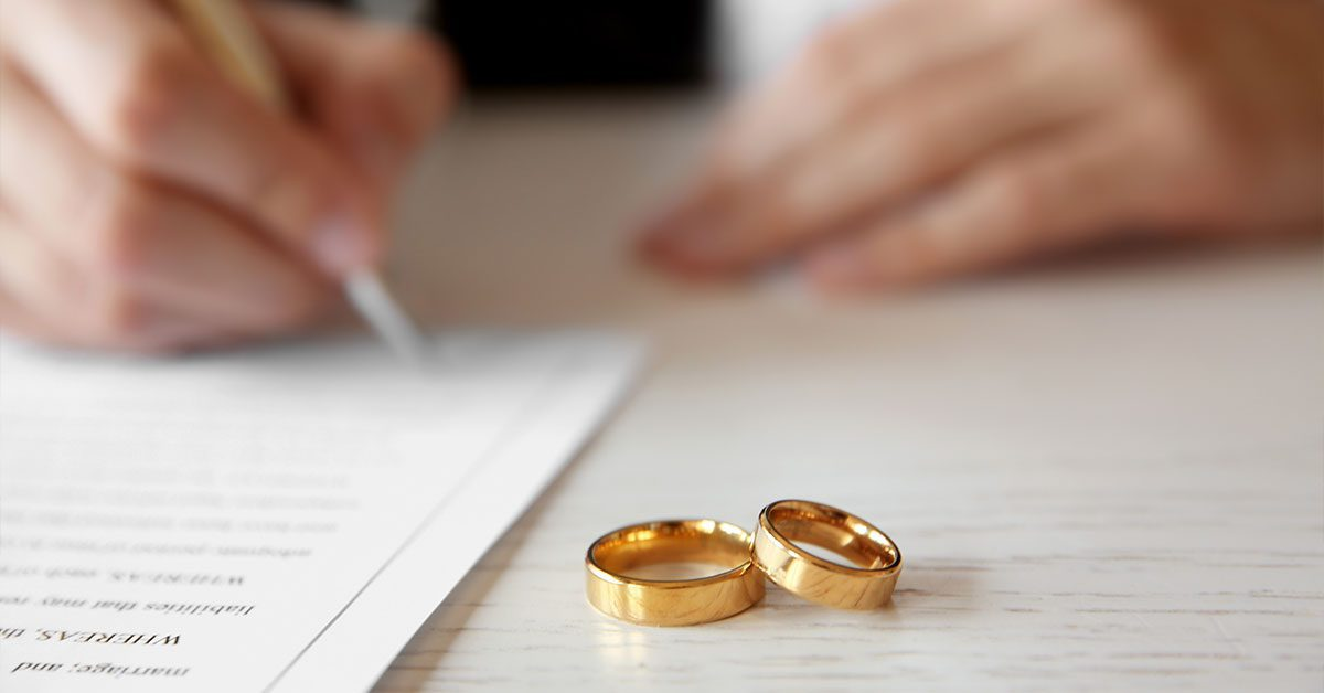 Signing a prenuptial agreement with gold wedding rings on the table