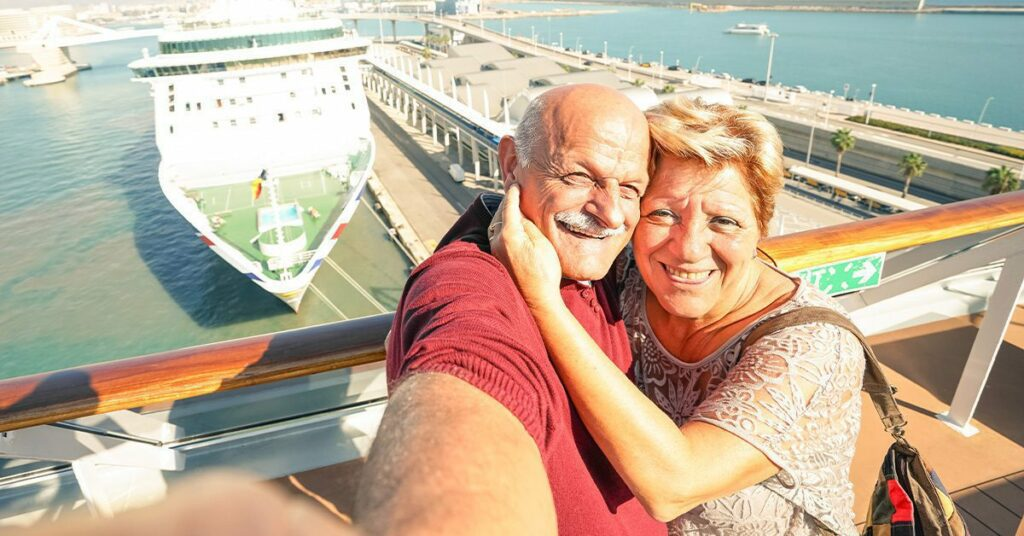 senior couple having a selfie in front of a cruise ship